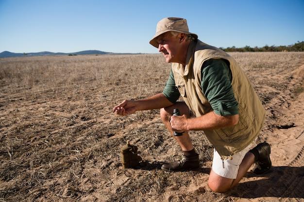 Человек с бинокулярным на коленях на пейзаж