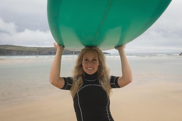 ビーチで頭にサーフボードを運ぶ幸せな女性サーファー