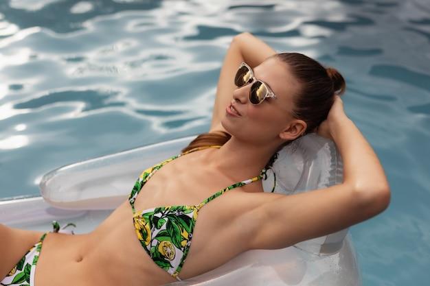 Женщина в бикини, расслабляющий на надувной трубе в бассейне