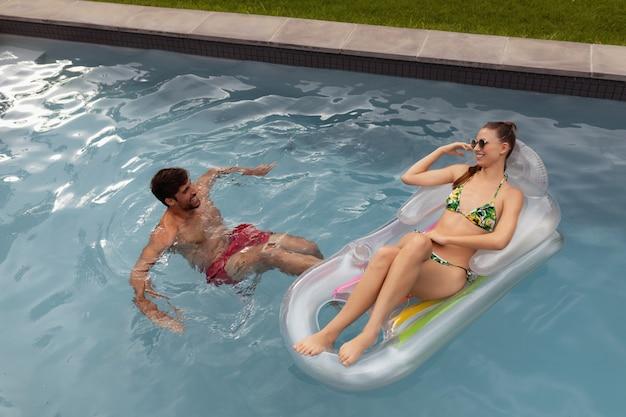 スイミングプールで一緒に楽しんでカップル