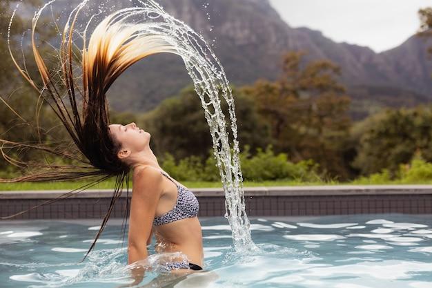 スイミングプールで彼女の髪を弾く女性