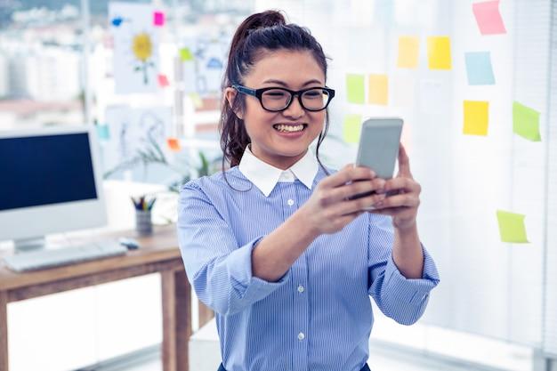 アジアの実業家のオフィスでスマートフォンを使用して