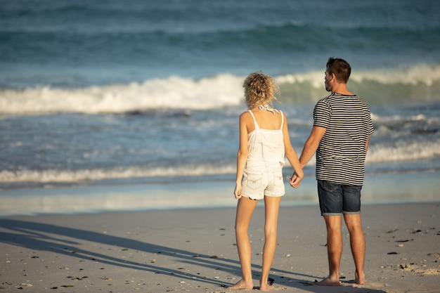 カップルは一緒にビーチで手をつないで立っています。