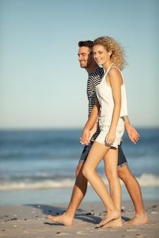 ビーチで手をつないで一緒に歩くカップル