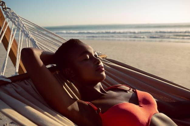 ビーチでハンモックで寝ている女性