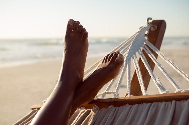 Женщина расслабляющий с ногами в гамаке на пляже