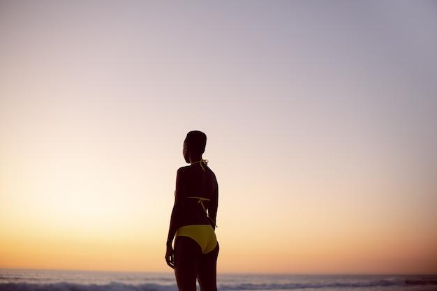 ビキニでビーチに立っている思いやりのある女性