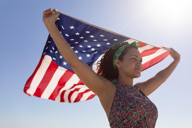 日差しの中でビーチにアメリカの国旗を振って美しい若い女性