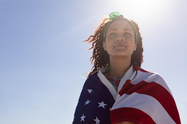日差しの中でビーチにアメリカ国旗に包まれた美しい若い女性