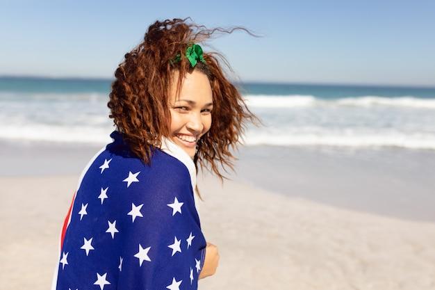 日差しの中でビーチでカメラを見てアメリカの国旗に包まれた美しい若い女性