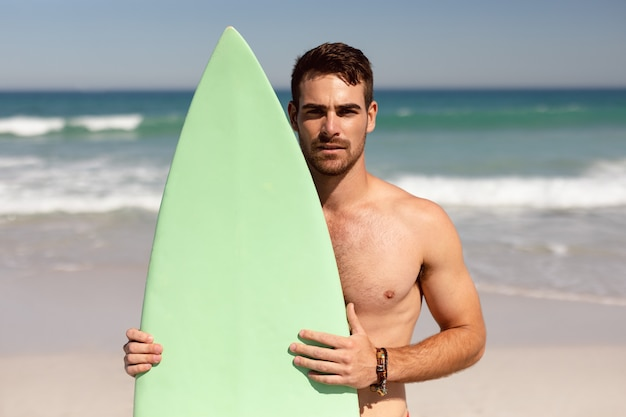 Без рубашки человек с доской для серфинга, глядя на камеру на пляже в лучах солнца