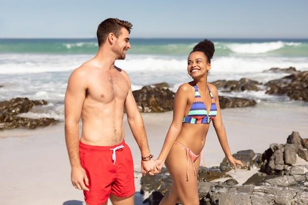 若いカップルが手を繋いでいると、太陽の下でビーチを歩いて