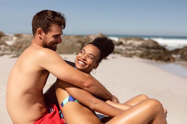 日差しの中でビーチで楽しんで若いカップル