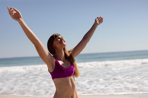日差しの中でビーチに立って腕を持つビキニで美しい女性