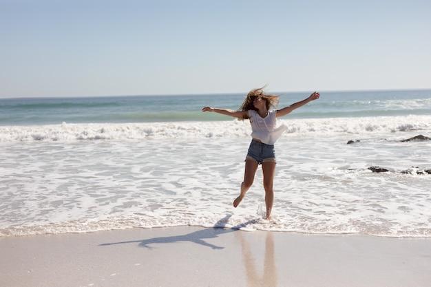 日差しの中でビーチを歩いて伸ばした腕を持つ美しい女性