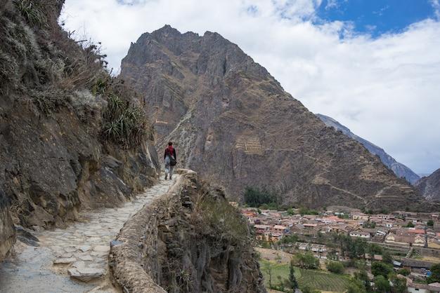ペルー、クスコ地方の聖地、オリャンタイタンボのインカトレイルと遺跡を探索する旅行者。南アメリカでの休暇と冒険。