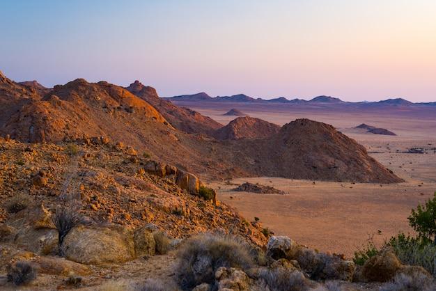 夕暮れ時、ナミブ砂漠、ナミビア、アフリカのカラフルな夕日で岩が多い砂漠