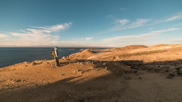 太陽の島の雄大なインカトレイルを探索するバックパッカー