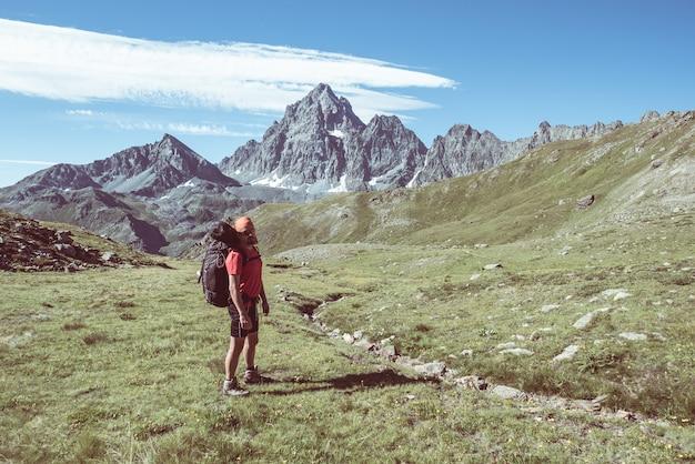 アルプスの高い夕日で輝く山頂の雄大な景色を見ている人。