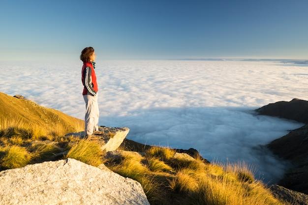 Женщины турист, достигнув своей цели на вершине горы и глядя на вид итальянских западных альп с облаками в долине ниже