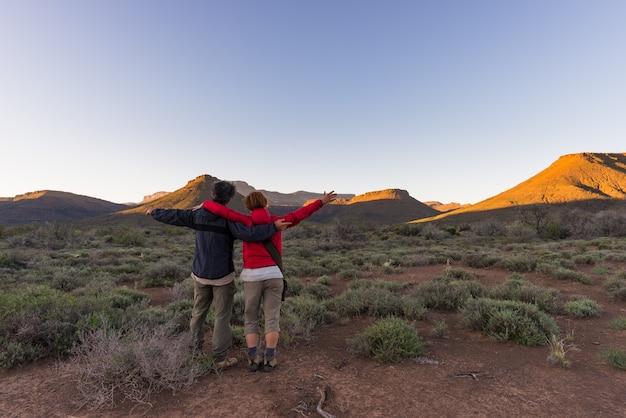 Обниматься пара с вытянутыми руками, наблюдая закат в национальном парке кару на закате