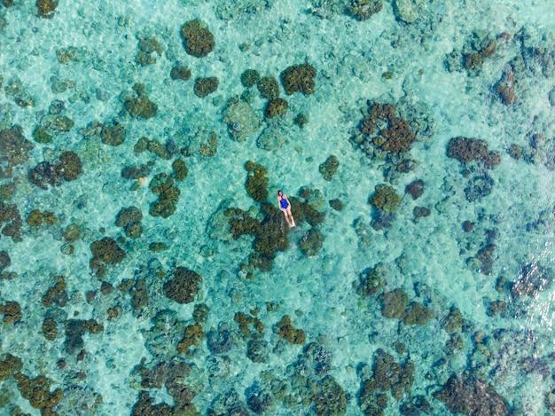 サンゴ礁の熱帯のカリブ海でシュノーケリングの人々を空中トップ