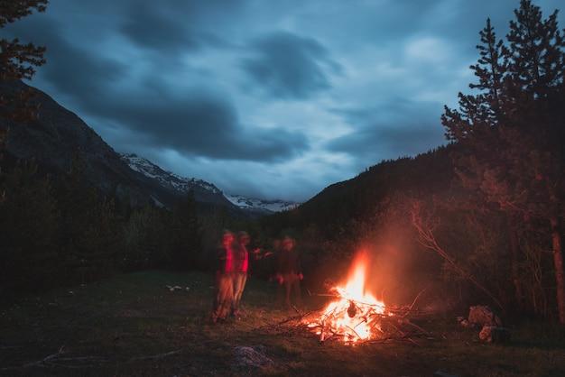 リモートのカラマツと松の木の森にキャンプの火を燃やす
