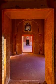 オレンジ色のトーンの廊下の壁と装飾された壁の並ぶドアと通路