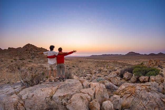 Обниматься пара с вытянутыми руками, наблюдая потрясающий вид на пустыню намиб, величественные достопримечательности в намибии.