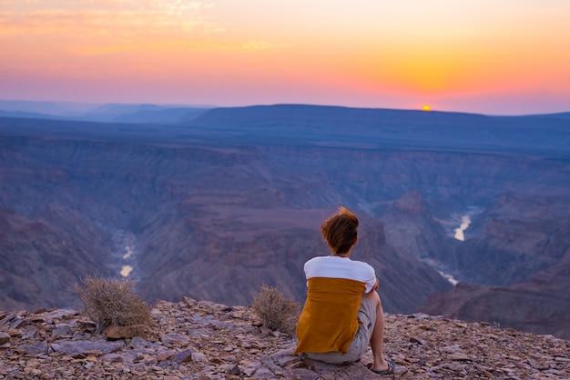 Вид сзади туриста, смотрящего на обширный вид на каньон фиш-ривер