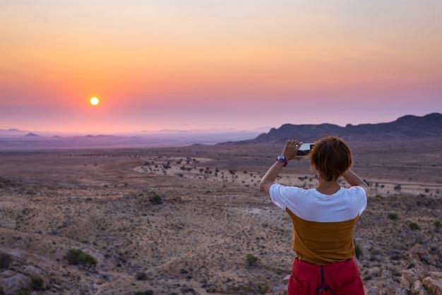 Турист фотографирует со смартфона потрясающий вид на бесплодную долину в пустыне намиб