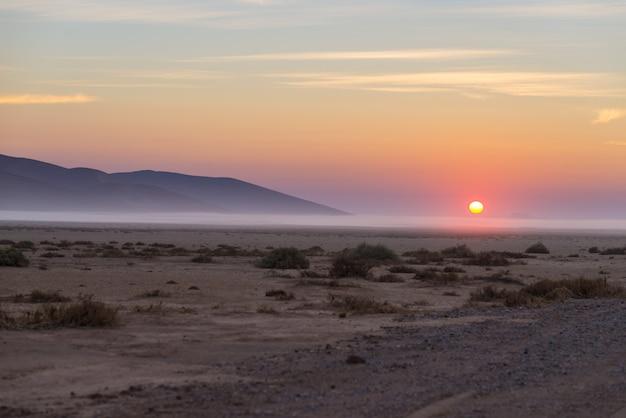 Восход солнца над пустыней намиб, проезд в прекрасном национальном парке намиб науклуфт, путешествия в намибию, африку.