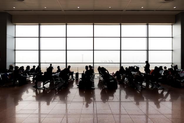 Люди сидят и ждут вылета в терминал аэропорта.