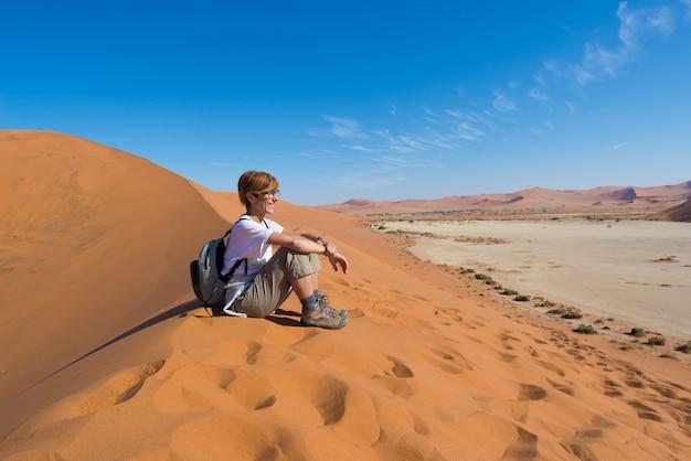 砂丘の上に座って、ナミブ砂漠のソススフレイ、アフリカのナミビアで最高の旅行先の見事な景色を見てリラックスした観光客。冒険と旅の人々の概念