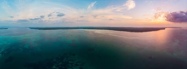 Небо карибского моря рифа острова вида с воздуха тропического пляжа драматическое на восходе солнца захода солнца. индонезия архипелаг молуккас, острова кей, море банда. лучшее место для путешествий, дайвинг и снорклинг