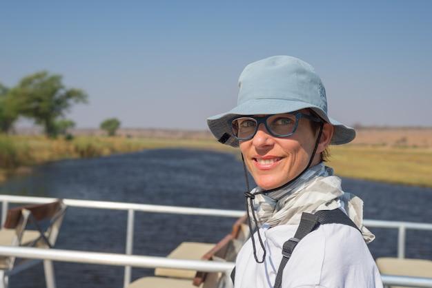 緑色の目と陽気な表情で笑顔の女性の肖像画。アフリカ、ナミビアのチョベ川を航行中に屋外で撮影された自然光、自然な肌。