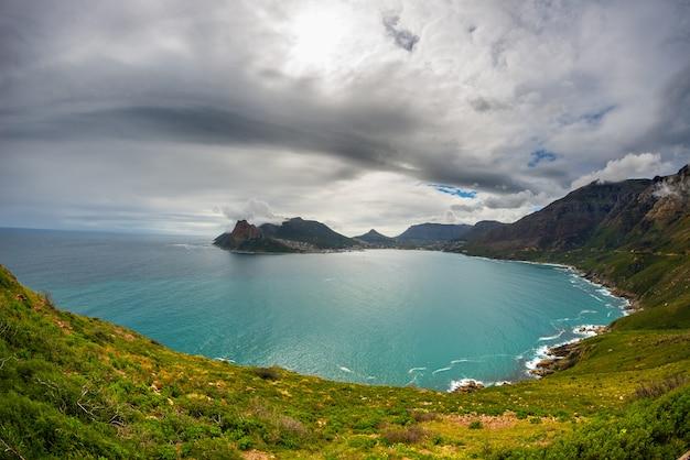 チャップマンズピークからの南アフリカ、ケープタウンのハウトベイの超広角魚眼レンズビュー。冬の季節、曇りの劇的な空。
