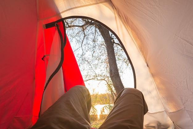 Глядя из интерьера палатки восход. приключенческие путешествия по африканским национальным паркам. мероприятия на свежем воздухе. человеческие ноги, открытая дверь.