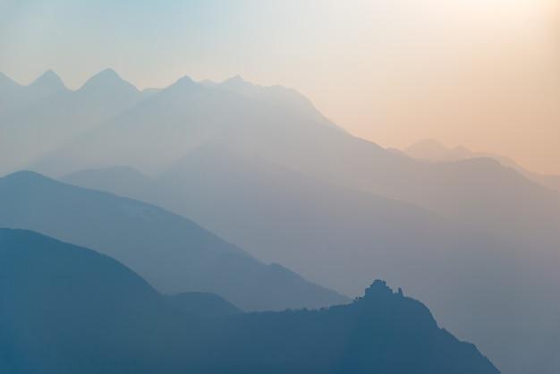 日没時の青いトーンの山のシルエットと修道院のプロファイル