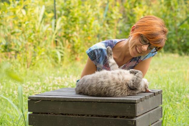 Женщина играет с кошкой на открытом воздухе в зеленом саду дома