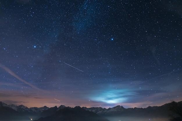 Ночь в альпах под звездным небом и лунным светом