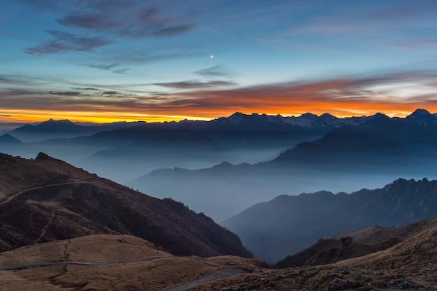 山のシルエットと夕日の見事な空