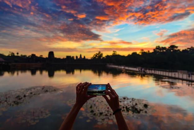一人の人がスマートフォンを持って夜明けにアンコールワットメインファサードシルエットを撮影