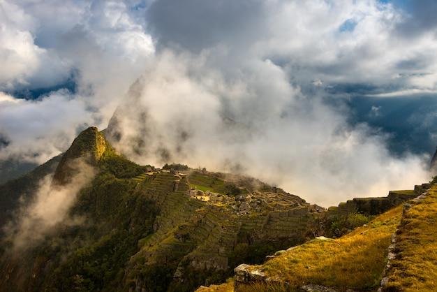 開いている雲からのマチュピチュの最初の日光