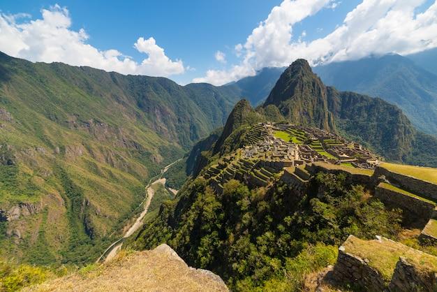 Мачу-пикчу освещается солнечным светом. широкоформатный вид с террас выше с живописным небом.