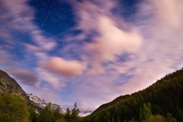 ぼやけた動きの雲と明るい月明かりの星空