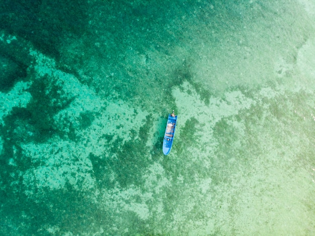 Воздушные сверху вниз лодка каноэ, плавающие на бирюзовый коралловый риф тропического карибского моря. индонезия архипелаг молуккас, острова кей, море банда. лучшее место для путешествий, лучший дайвинг с маской и трубкой.