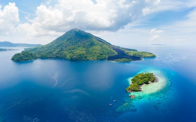 Аэрофотоснимок острова банда молуккский архипелаг индонезия, пулау гунунг апи, лавовые потоки, пляж с белым песком кораллового рифа. лучшее туристическое направление, лучший дайвинг с маской и трубкой.