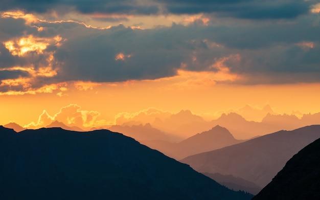 日の出のアルプス。カラフルな空の雄大な山々の峰、霧の谷。上からのサンバーストとバックライトの拡大図。