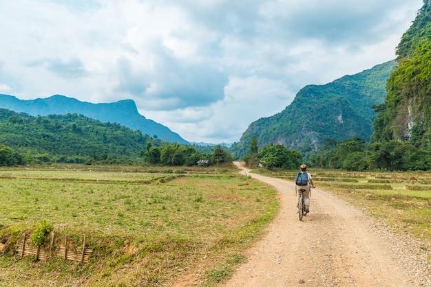 ラオスのヴァンヴィエンバックパッカー旅行先の周りの風光明媚な風景の未舗装の道路でマウンテンバイクに乗る女性